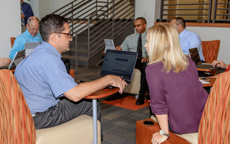 Two employees discussing statistics on laptop